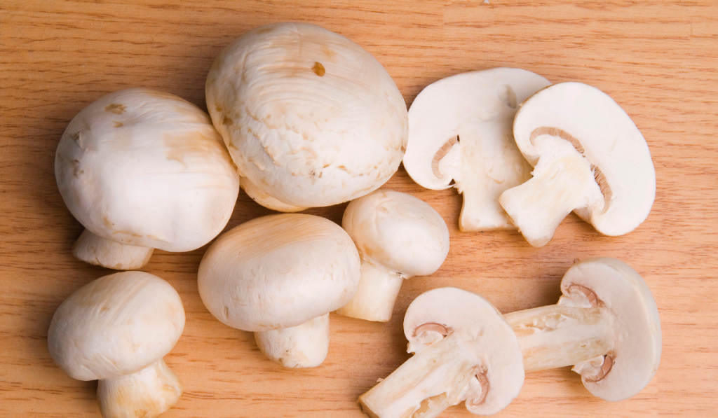 Mushrooms on a brown wooden chopping board.